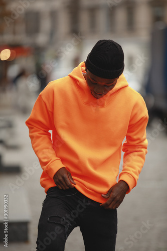 Handsome African man model wearing empty bright orange hoodie in city Wall mural