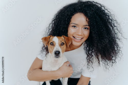 Fotomural  Close up shot of beautiful happy Afro woman with bushy curly hair, embraces favo