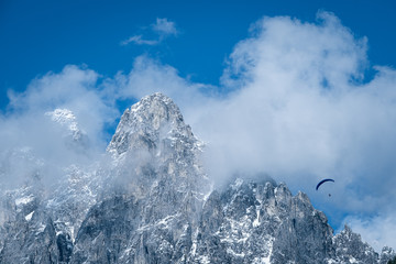 paragliding flies through the clouds over the rocky alps