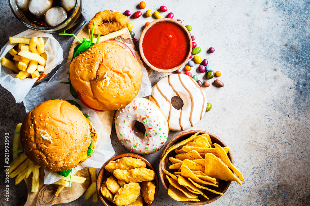Fototapety, obrazy: Assortment of fast food. Junk food background. Cheeseburgers, french fries, nachos, donuts, soda and nuggets on gray background, top view.