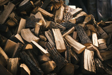Pile Of Firewood On A Heap. Coniferous And Deciduous Stacks Of Firewood.