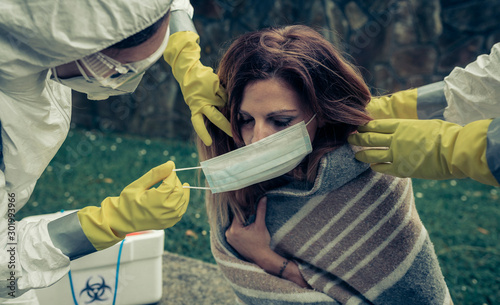 Man and woman in bacteriological protective putting a mask on sick woman Wallpaper Mural
