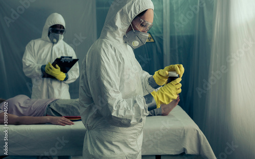 Leinwand Poster  Doctors with bacteriological protection suits preparing medication for sick woma