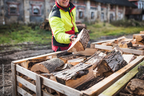 Foto Man collects a pile of firewood on a heap