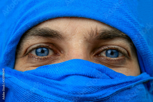 Photo close up of the blue eyes of a man whose face is covered with a blue bandage