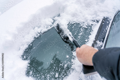 Obraz Hand are holding and brushing car window clean of snow. car covered in snow during heavy snow fall. Winter and seasonal concept. - fototapety do salonu