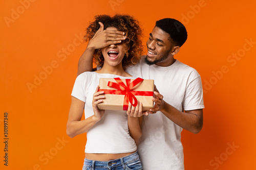 Loving black guy surprising his girlfriend with gift Billede på lærred