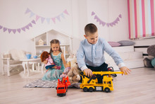 Beautiful Happy Caucasian Children Playing In Their Room, Boy Playing With Cars, Girl Playing With Dolls
