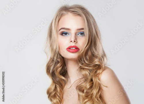 Cute blonde model woman with long healthy curly hair