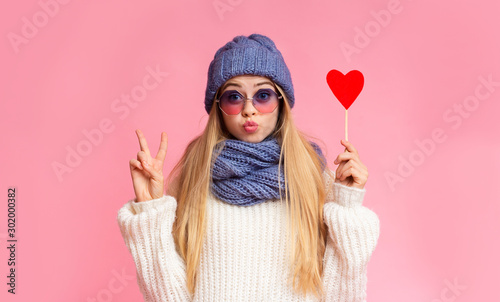 Cute girl showing peace sign, holding red heart card - 302000382