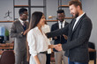 Side view on caucasian people shaking hands. Beautiful woman with long black hair in meeting with caucasian leader of company, man in tuxedo shake hand to her