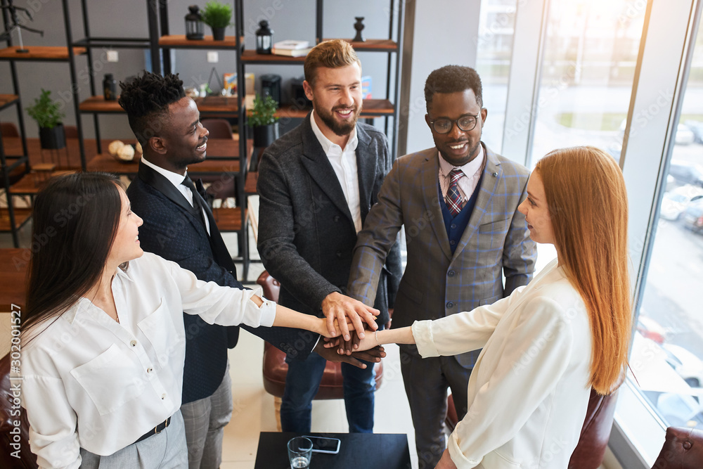 Fototapeta Happy business people together in office joined hands in modern office, caucasian and african business people in formal wear