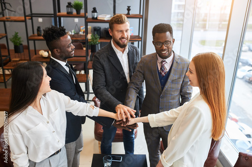 Photo  Happy business people together in office joined hands in modern office, caucasia