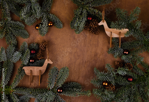 Poster Cerf Two wooden deer toys on a brown background surrounded by live branches of spruce and Christmas toys. Place for text or design.