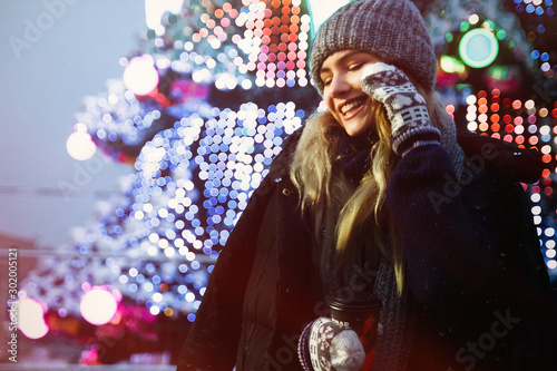 photo with grain and aberrations under the old photo, film photo beautiful girl in a hat with coffee in the evening, basks, near the Christmas tree, winter holidays, holiday and walks Canvas Print