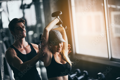 Fotomural  Athletic fitness woman pumping up muscles with dumbbells, Fit woman working out