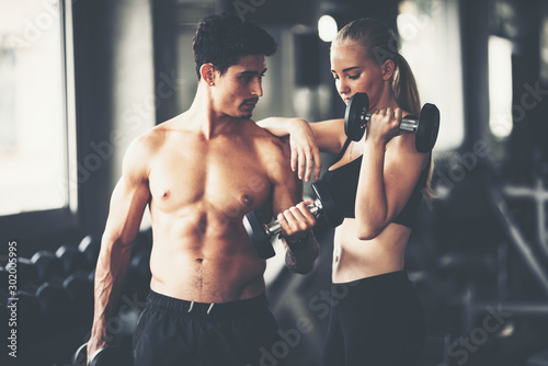 Cuadros en Lienzo  Fitness couple - woman and man in sport gym