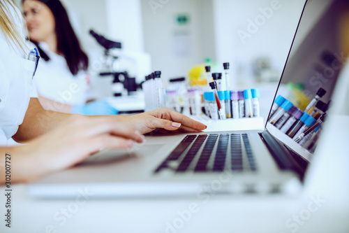 Foto  Close up of female lab assistant in white uniform sitting in lab and using laptop for data entry