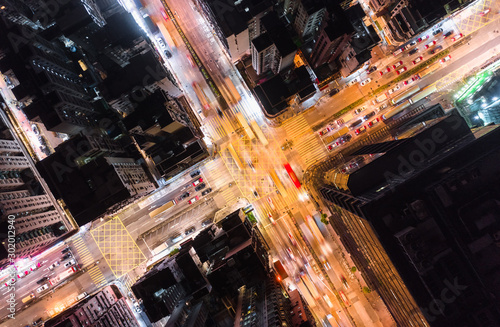 Fotomural Car, taxi, and bus traffic on road intersection at night in Hong Kong downtown district, drone aerial top view
