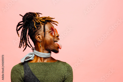 Fun studio profile portrait of trendy young man with sunglasses and  tongue out Wallpaper Mural