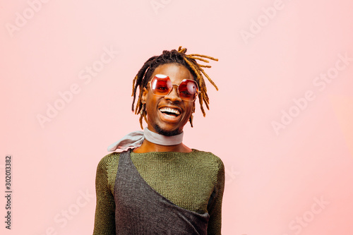 Photo Portrait of a happy and cheerful young man laughing, isolated on pink
