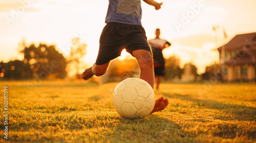 Fotografía  Action sport outdoors of kids having fun playing soccer football for exercise in community rural area under the twilight sunset sky
