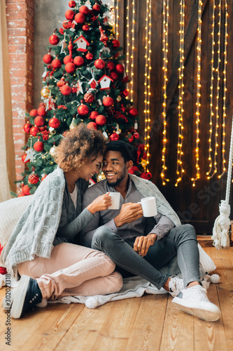 Young couple drinking coffee and enjoying Christmas morning - 302021318