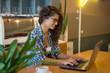 Modern business woman is using laptop in coffee shop.