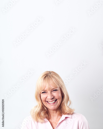 Studio Shot Of Smiling Mature Woman Against White Background At Camera - 302025924