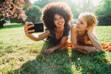 Couple of young women take a selfie with the smart phone lying on the grass of a meadow on a summer day at the park - Millennials have fun together laughing and joking