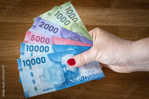Fotografía  Chilean pesos, banknotes in a woman's hand