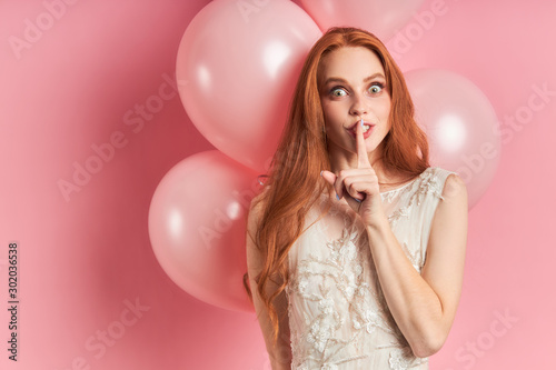 Attractive surprised woman with auburn hair stand in coquettish gesture Wallpaper Mural
