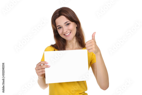 Young woman with blank sheet of paper and thumb up on white background Fototapet