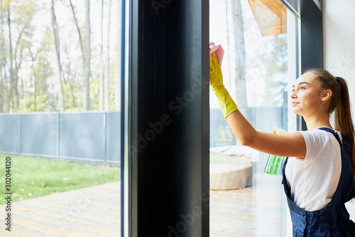Industrious woman with rug, wearing yellow rubber gloves do cleaning of window glass. panoramic window