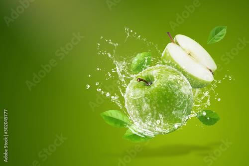 Water splashing on Fresh green apple on Green background