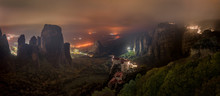 Meteora Mountains And Monasteries Lit At Night Over Kastraki City Glowing In Distant Fog