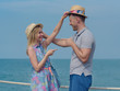 Cute European loving couple in sun hats having fun on the pier near clear blue sea, they smiling, pointing to each other and looking to each other and changing their hats. They are on their honeymoon.