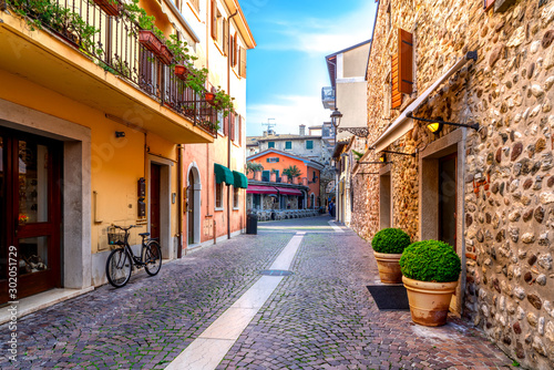Obraz Narrow street in the old town of Bardolino on a sunny day in autumn - fototapety do salonu