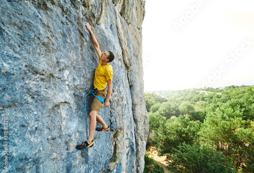 Slika na platnu Young strong man climbing challenging route on a high vertical limestone cliff