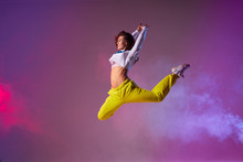 Pleasant Playful Woman With Long Curly Brunette Hair, Bright Yellow Pants, White Pullover, Wearing Stylish Sneakers, Showing Dance Element In Club Stage Full Of Colourful Smoke