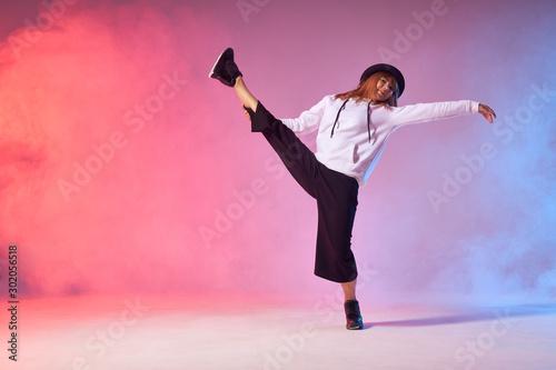 Flexible young dancer doing split leap in the air, raising leg intensively up, b Fototapet