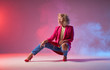 canvas print picture - Slim tanned woman dressed in stylish clothes, and red heels, sitting on squat, looking away, showing dancing element on studio background, jazz funk street hip hop music
