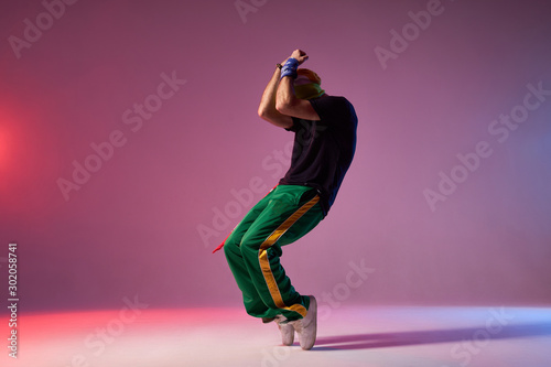 Modern hip hop dancer frozen in movie, standing on tiptoe, covering head with ha Canvas Print