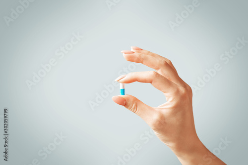 Obraz Female hand holding a capsule pill or vitamin. - fototapety do salonu