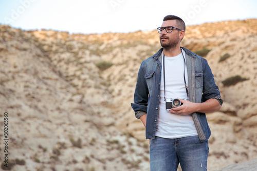 Hombre joven con lentes y ropa vaquera sujetando cámara de fotos analógica al ai Canvas Print