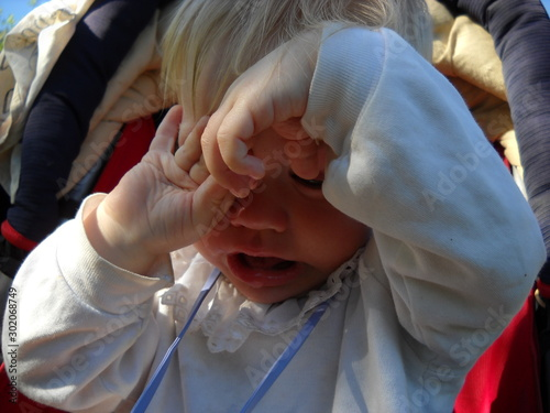 Photo Petrozavodsk, Republic of Karelia / Russia - June 8, 2019: a small child sits in a stroller and rubs his face with his hands