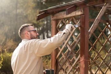 Mężczyzna w ogrodzie maluje na brązowo drewniane deski mebla ogrodowego. Odnawianie i  konserwacja pergoli ogrodowej.