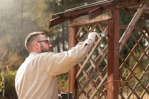 Mężczyzna w ogrodzie maluje na brązowo drewniane deski mebla ogrodowego Canvas Print