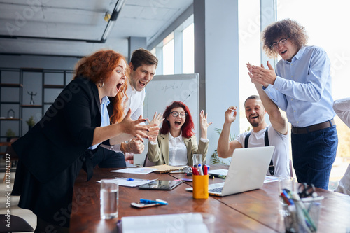 Fototapety, obrazy: Cheerful group of happy business people after winning in formal wear gesturing, with fists in the air, clapping hands and hug. Business people, business team, co-working concept