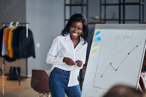 Fototapeta Positive african business lady in white shirt and blue jeans stand talking explaining making flip chart presentation for younger leaders, share business experience with smile obraz